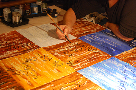 Liz Mathews lettering an artist's book with a driftwood stick (Autumn Farewell from Burns' Year: Love and Freedom, now in the National Library of Scotland). Photo by Frances Bingham.